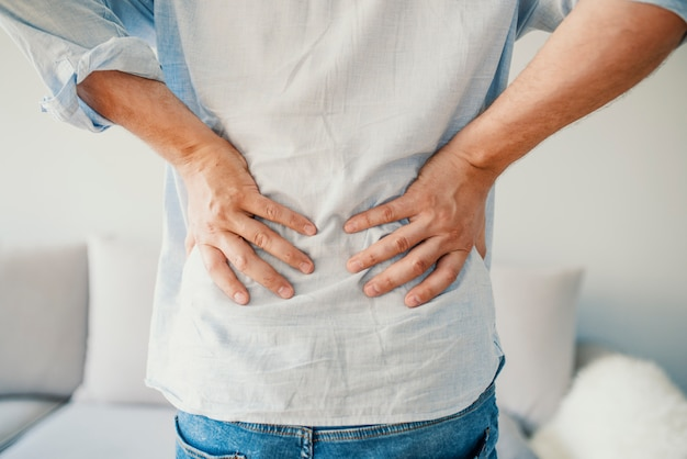 Unglücklicher mann, der zu hause unter rückenschmerzen leidet
