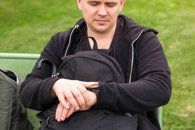 Unglücklicher mann mit rucksäcken, der auf öffentliche verkehrsmittel in der stadt wartet, schaut er auf seine uhr. pendeln, reisen, transportkonzept