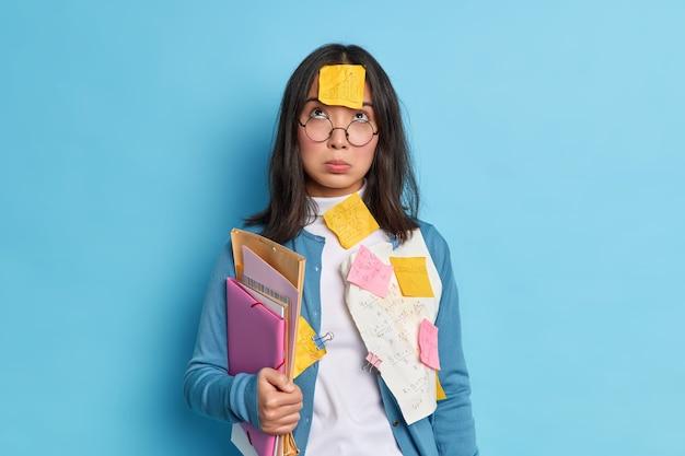 Unglücklicher müder asiatischer student, der oben konzentriert ist, hat traurigen ausdruck, trägt eine brille zur sehkorrektur hält ordnerpapiere, die mit büroklammern geklebt werden.