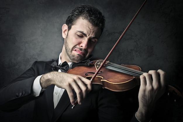Unglücklicher musiker, der auf einer violine spielt