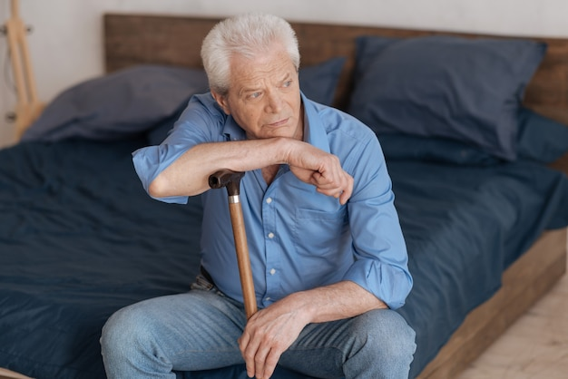 Unglücklicher nachdenklicher älterer mann, der auf dem bett sitzt und einen spazierstock hält, während er sich darauf stützt