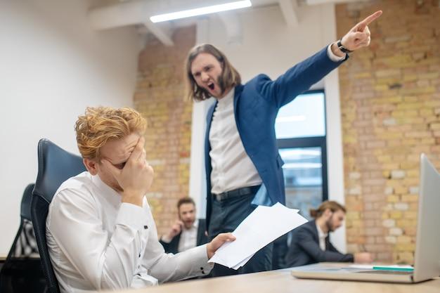 Unglücklicher rothaariger mann mit papieren, die sein gesicht mit der hand bedecken, die am laptop und wütenden schreienden kollegen sitzt