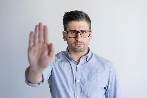 Unglücklicher unbefriedigter junger mann mit der stoppel, die ablehnungszeichen zeigt und kamera betrachtet.
