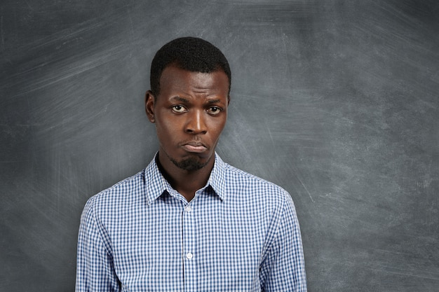 Unglücklicher und trauriger afrikanischer student verzog das gesicht und war unzufrieden mit seinem versagen bei den prüfungen. junger unzufriedener schwarzer lehrer enttäuscht von den prüfungsergebnissen.