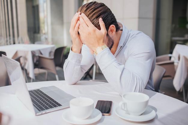Unglücklicher und trauriger junger mann sitzt am tisch im restaurant. er schloss sein gesicht mit den händen. guy ist emotional. es gibt zwei tassen und ein telefon mit laptop am tisch.