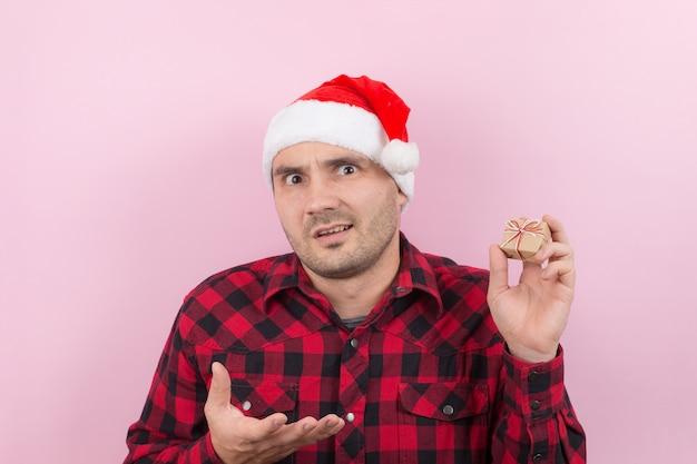 Unglücklicher, verärgerter mann in einem roten hut hält ein kleines geschenk mit ekel auf seinem gesicht