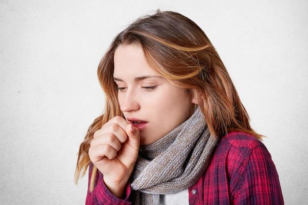 Unglücklicher weiblicher husten, der bei frostigem wetter erkältet ist, trägt einen warmen schal am hals