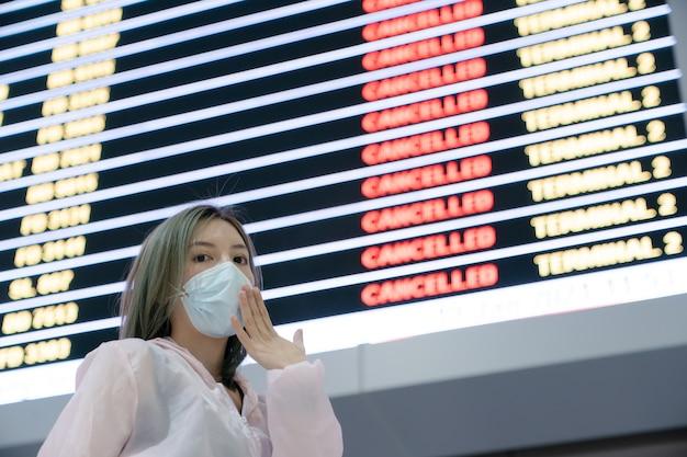 Unglücklicher weiblicher reisender, der maske trägt, die flugstornierungsstatus auf fluginformationstafel im flughafen sucht