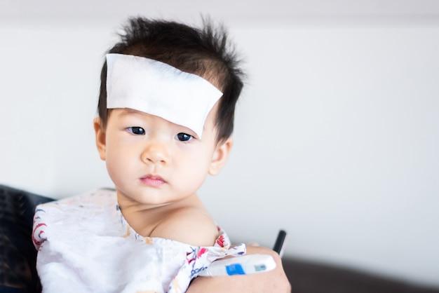 Unglückliches asiatisches kleines baby krank mit kühlem fiebergelee auf stirn