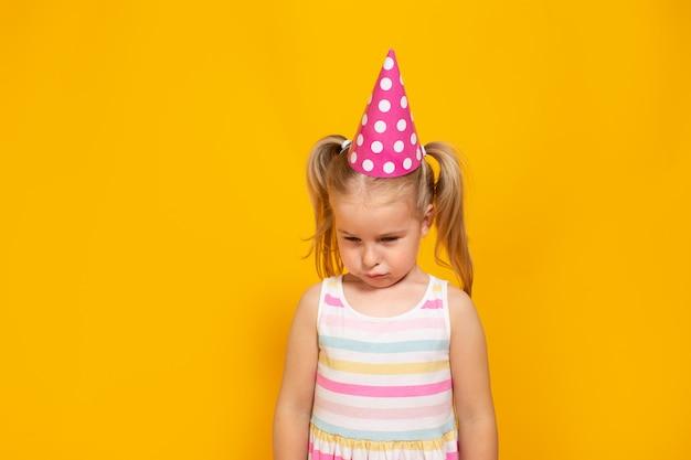Unglückliches blondes kaukasisches mädchen mit traurigem oder langweiligem gesicht auf gelber wand. schlechte geburtstagsfeier.