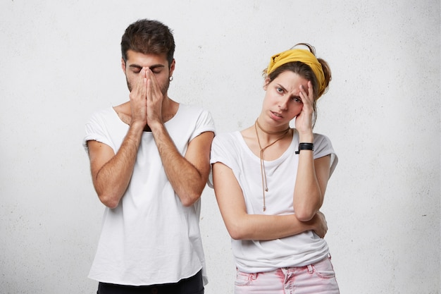 Unglückliches depressives junges paar, das sich gestresst fühlt, mit finanziellen problemen konfrontiert ist oder streit oder streit hat: mann bedeckt sein gesicht, während frau ihre stirn berührt und frustriert aussieht