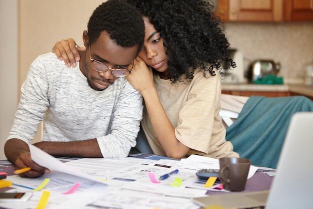 Unglückliches junges afrikanisches paar, das finanziellem stress gegenübersteht