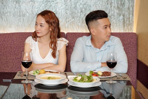 Unglückliches junges paar, das beim abendessen nicht spricht, nachdem es konflikte und beziehungsprobleme hatte