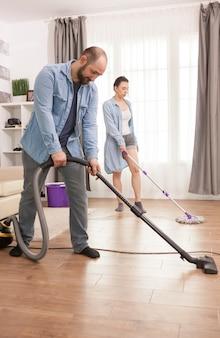 Unglückliches junges paar, das wohnzimmerboden säubert