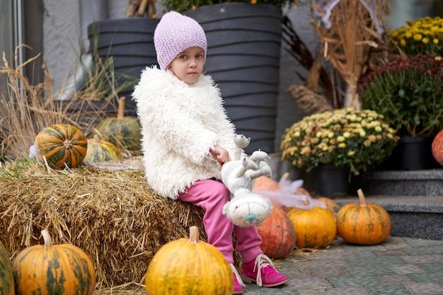 Unglückliches kleines mädchen, das im freien halloween kürbis mit spielzeugkatze herbstsaison kaukasisches weibliches kind losy in der stadt sitzt, die traurig einsam sitzt