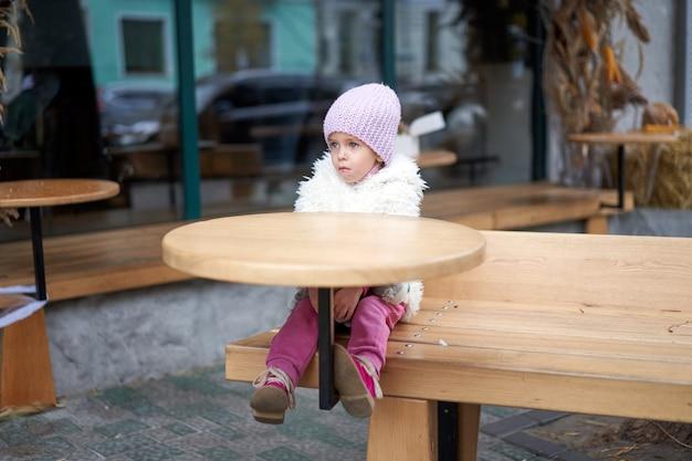 Unglückliches kleines mädchen, das im freiencafé an der tischherbstsaison sitzt kaukasisches weibliches kind losy in der stadt, die traurig einsam sitzt