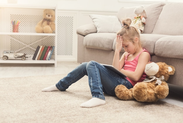 Unglückliches kleines mädchen, das online-spiele auf digitalem tablet spielt. trauriges weibliches kind, das mit ihrem teddybären auf dem boden in der nähe des sofas sitzt. schockierende inhalte und social-networking-konzept