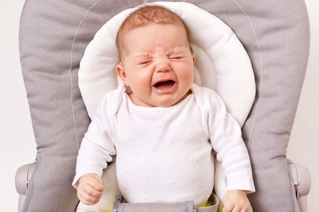 Unglückliches kleines säuglingsmädchen oder -junge, der im türsteherstuhl weint