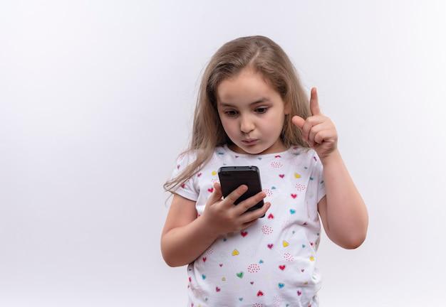 Unglückliches kleines schulmädchen, das weißes t-shirt trägt, das auf telefon zeigt, zeigt auf isolierte weiße wand