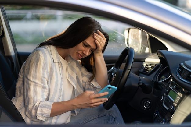 Unglückliches mädchen weint beim lesen einer sms-nachricht im smartphone, das auto fährt, verärgert die weibliche trennung von ihrem freund