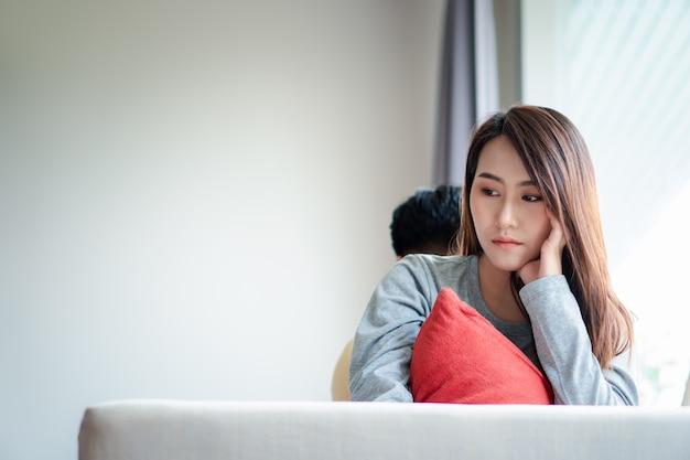 Unglückliches paar sitzt hintereinander auf der couch und vermeidet es, miteinander zu reden oder sich anzusehen