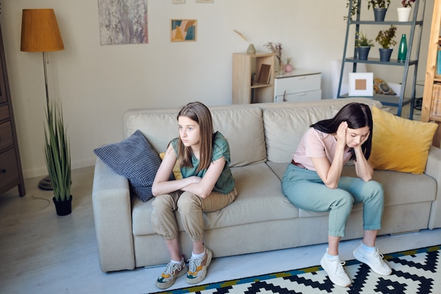Unglückliches teenager-mädchen mit verschränkten armen und ihrer gestressten mutter mit dem kopf in den händen, die während eines streits oder konflikts auf der couch sitzt