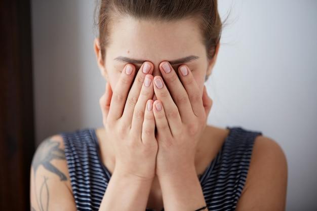 Unglückliches überwältigtes mädchen, das kopfschmerzen schlechten tag hat, hält hände auf gesicht