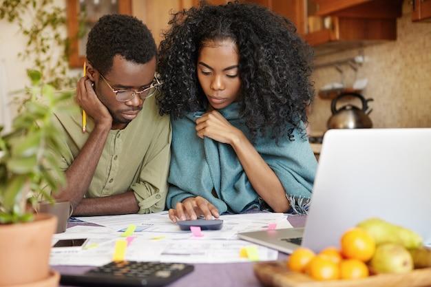 Unglückliches und depressives junges afroamerikanisches paar, das das familienbudget berechnet