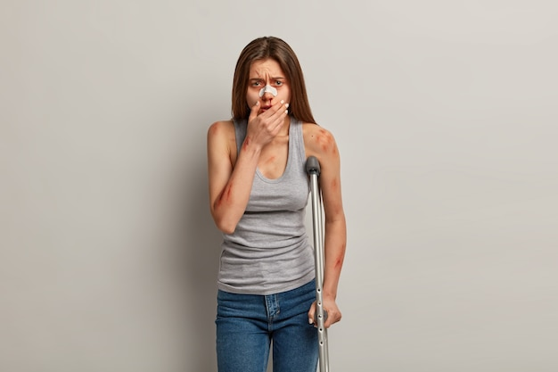 Unglückliches weibliches opfer hat eine blutende nase und verschiedene kratzer am körper nach einem schrecklichen verkehrsunfall, knochenbrüche, bewegt sich mit krücken, sieht verzweifelt aus, isoliert auf grauer wand