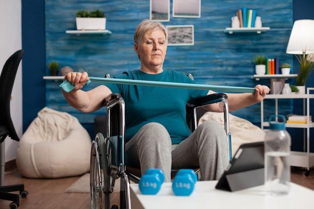 Ungültige ältere frau, die den armmuskelwiderstand mit einem gummiband trainiert, das fitnessvideos auf dem tablet ansieht