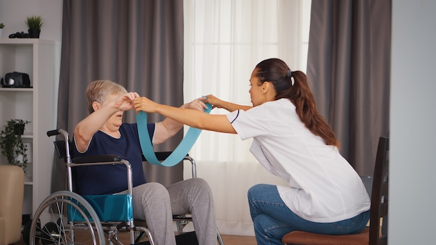 Ungültige ältere frau im rollstuhl, die mit hilfe des arztes eine reha durchführt. training, sport, erholung und heben, altenheim, gesundheitspflege, gesundheitsförderung, sozialhilfe, do