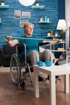 Ungültige ältere frau im rollstuhl, die widerstandsgummiband hält, das körpermuskel ausdehnt