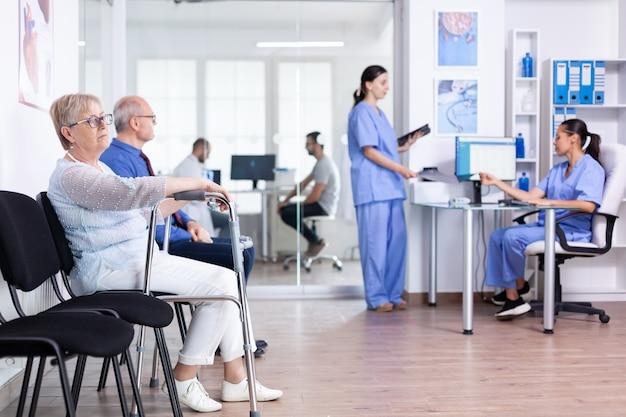 Ungültige ältere frau in der krankenhauslobby mit gehhilfe
