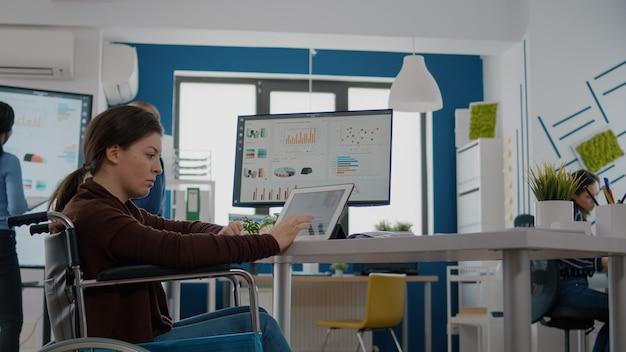 Ungültige, gelähmte, behinderte unternehmerin, die computer und tablet gleichzeitig verwendet, um den sta...