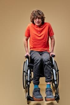 Ungültige männer versuchen akribisch, auf beinen zu stehen und den körper ohne unterstützung anzuheben. isolierter beiger hintergrund