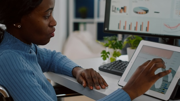 Ungültige managerin, die im rollstuhl mit computer und tablet gelähmt ist und gleichzeitig für ein finanzprojekt im büro für unternehmensgründungen arbeitet