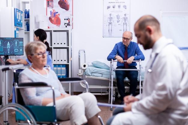 Ungültiger älterer mann mit gehhilfe in einer belebten modernen privaten genesungsklinik