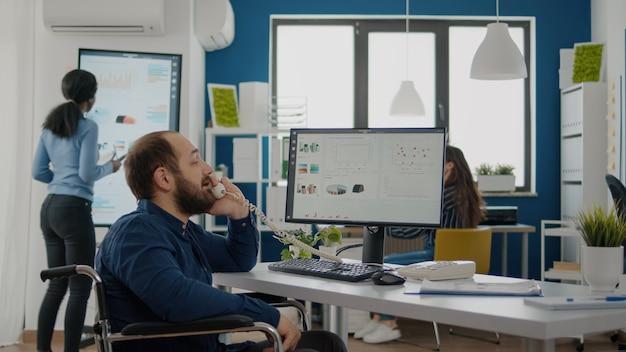 Ungültiger behinderter behinderter geschäftsmann, der im rollstuhl sitzt und am computer arbeitet, mit finanzstatistiken, die am telefon antworten