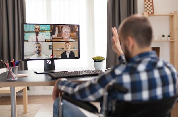 Ungültiger freiberufler im rollstuhl während eines videoanrufs, der von zu hause aus arbeitet. junger immobilisierter geschäftsmann, der sein geschäft online macht, high-tech verwendet, in seiner wohnung sitzt und aus der ferne in sp . arbeitet