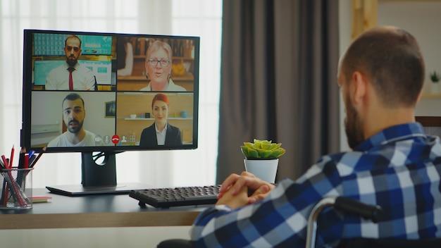 Ungültiger freiberufler im rollstuhl während eines videoanrufs, der von zu hause aus arbeitet.