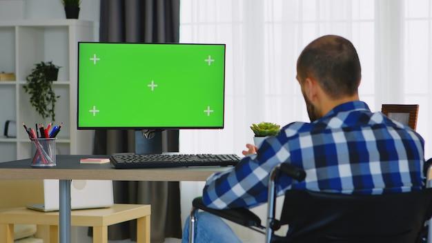 Ungültiger geschäftsmann, der während eines videoanrufs auf einem computer mit grünem bildschirm winkt.