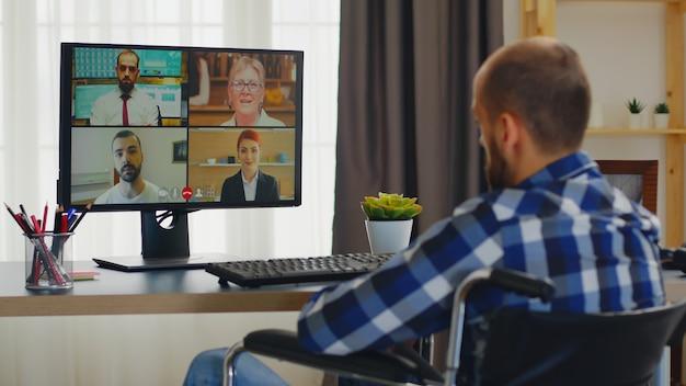 Ungültiger mann im rollstuhl begrüßt menschen während eines videoanrufs, der von zu hause aus arbeitet.