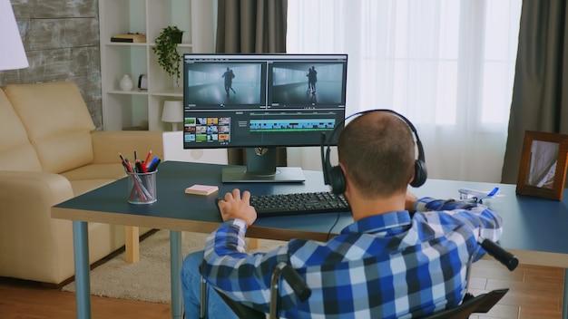 Ungültiger mann im rollstuhl, der ein video mit postproduktionssoftware bearbeitet und kopfhörer trägt.