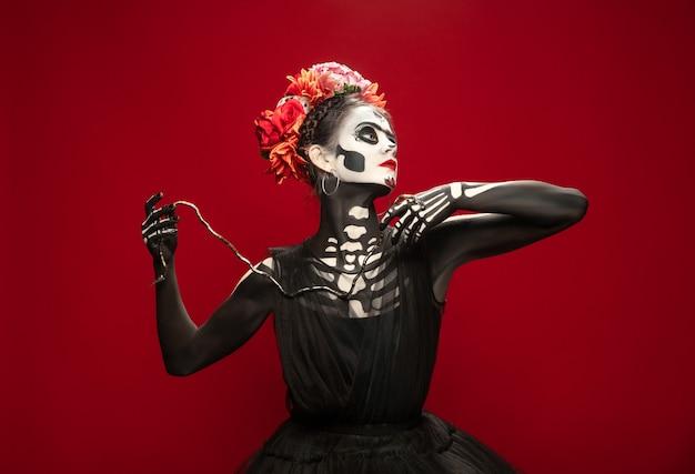 Unheimlich. junges mädchen wie santa muerte saint death oder sugar skull mit hellem make-up. porträt auf rotem studiohintergrund mit exemplar isoliert. feiern von halloween oder tag der toten.
