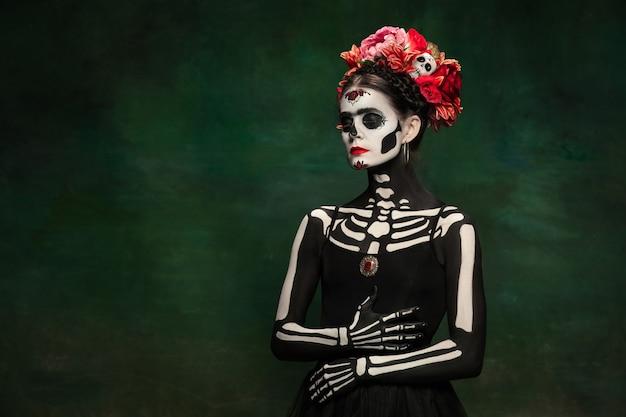 Unheimlich. junges mädchen wie santa muerte saint death oder sugar skull mit hellem make-up. porträt lokalisiert auf dunkelgrünem studiohintergrund mit exemplar. feiern von halloween oder tag der toten.