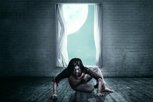 Unheimliche zombies mit blut und wunden auf seinem körper, die auf dem verlassenen haus kriechen