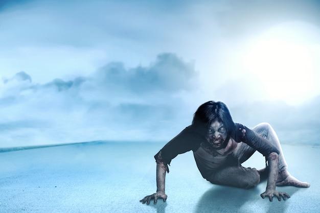 Unheimliche zombies mit blut und wunden auf seinem körper, die auf der asphaltstraße kriechen