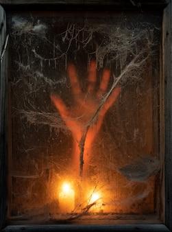 Unheimlicher halloween-hintergrund mit gruseligen spinnweben und hand im dunkeln