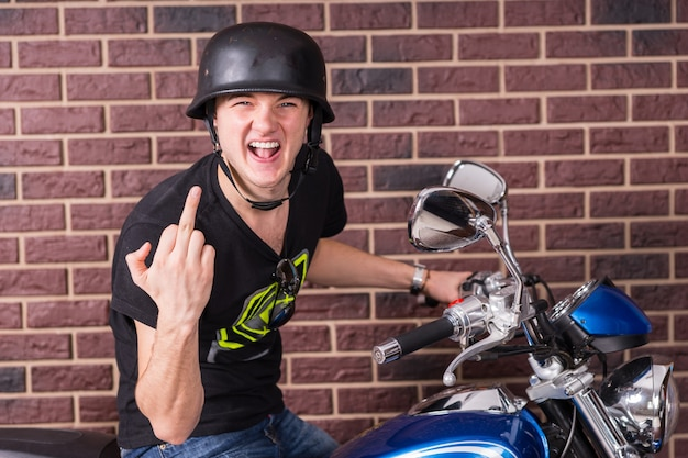 Unhöflicher aggressiver junger mann, der auf seinem motorrad in seinem helm sitzt und eine unhöfliche beleidigende geste mit seinem mittelfinger macht, während er in die kamera schreit