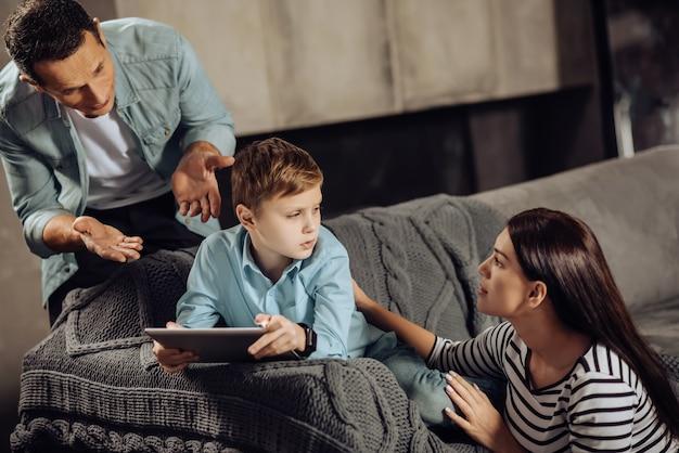 Unhöfliches kind. der weithaarige teenager spielt auf dem tablet und schnappt wütend nach seinen eltern, während sie versuchen, ihn davon zu überzeugen, mit dem binge-play aufzuhören